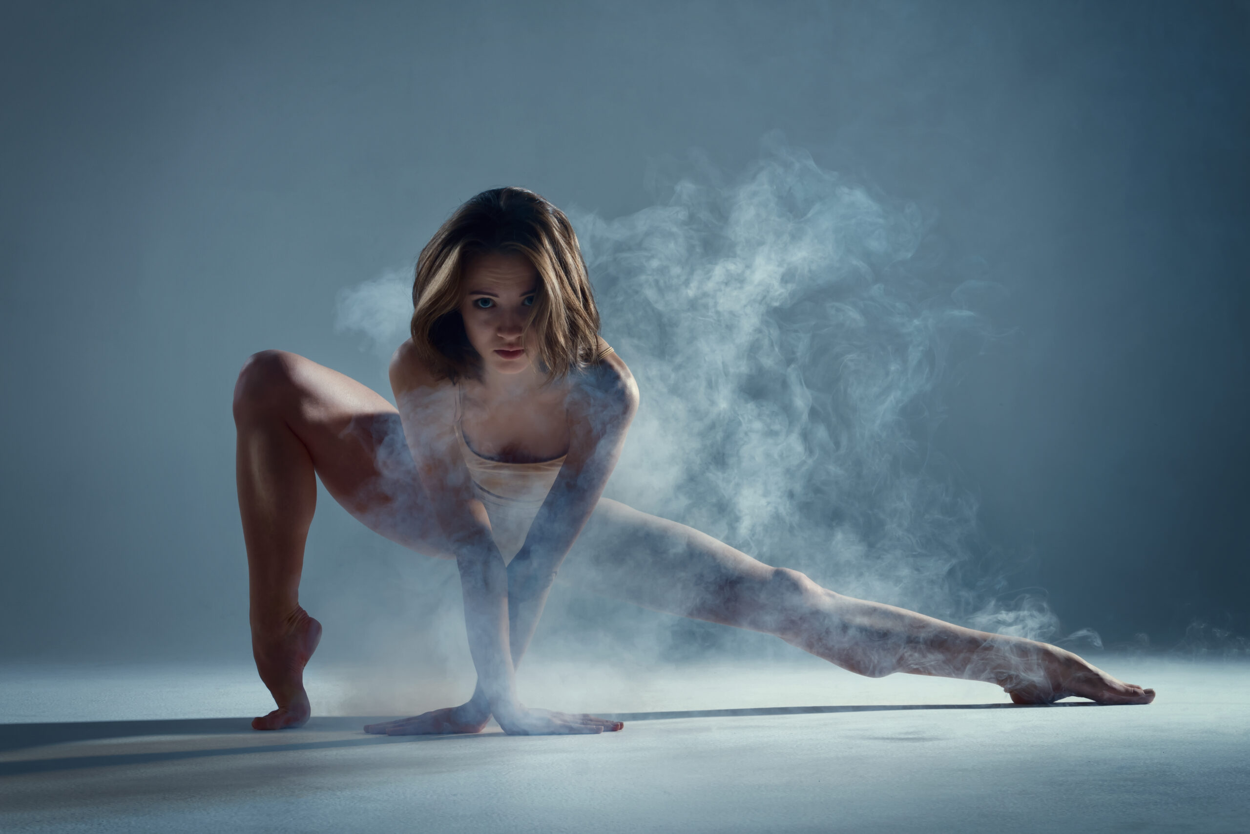Dancing in cloud concept. Muscle brunette beauty female girl adult woman dancer athlete in fog smoke fume wearing dance bodysuit making sexy dance element performance on isolated grey background