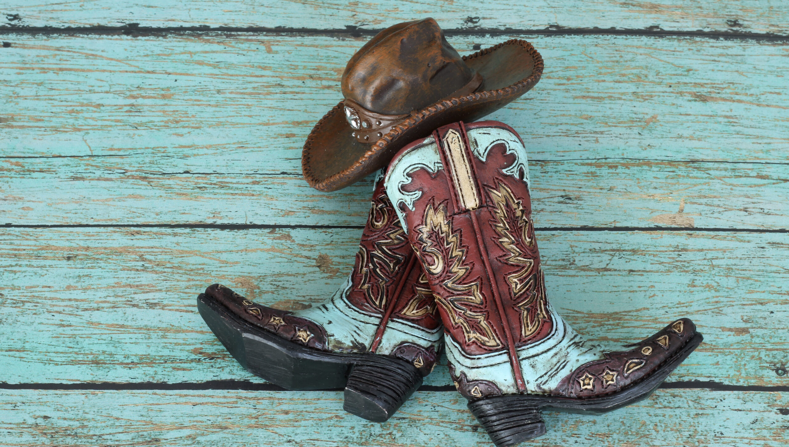 cowboy boots and hat laying on a teal background with copy space